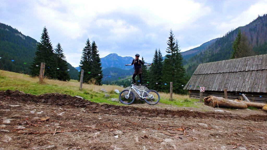 Osoba stoi na kamieniu. Obok opart rower a w tle góry