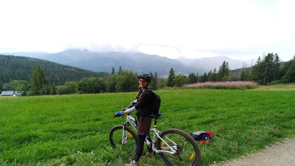 Rowerzystka na zielonej trawie a w tle tatry