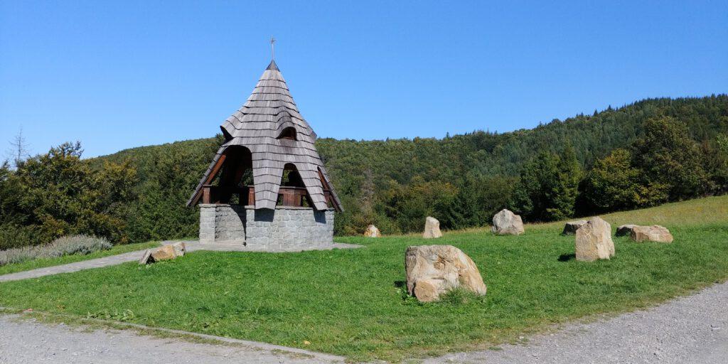 dzwonnica Św. Izydora Oracza z Madrytu. Drewniana okrągła wiata na zielonej trawie