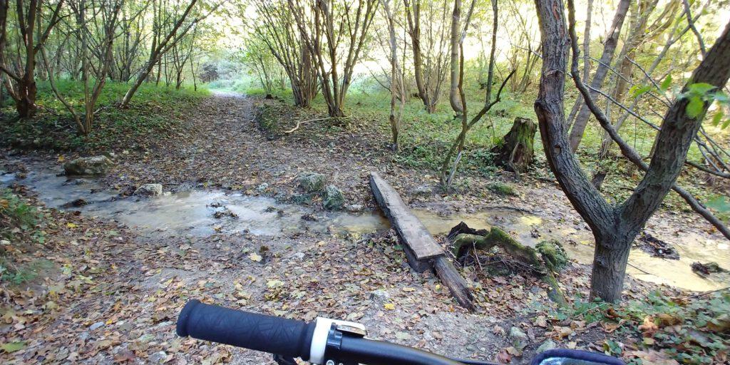 prowizoryczny mostek na rzece i kierownica roweru