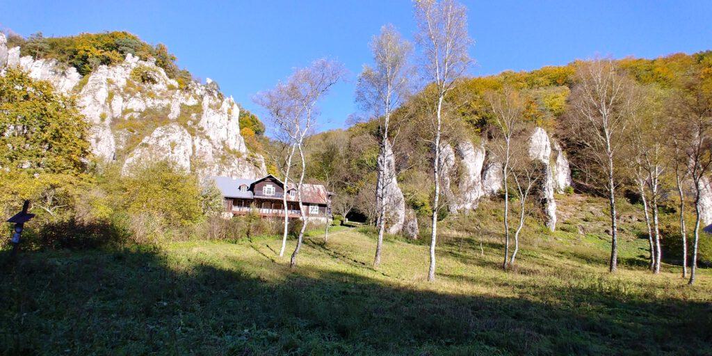 drewniana chata pod wapiennymi skałami na tle niebieskiego nieba