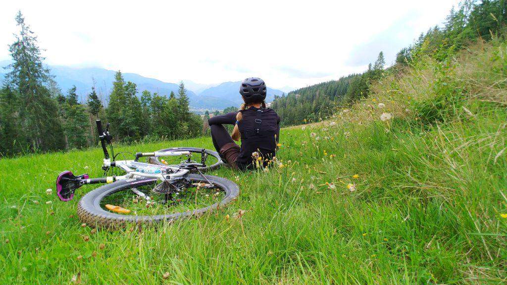 Dziewczyna na łace z rowerem siedzi na zielonej trawie