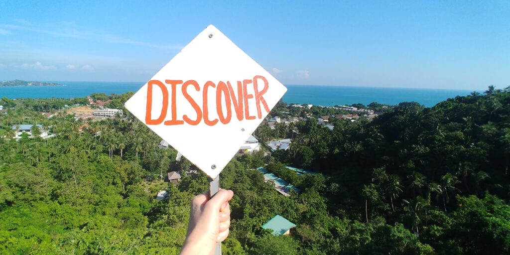 tabliczka z napisem Discover na tle dżungli i morza