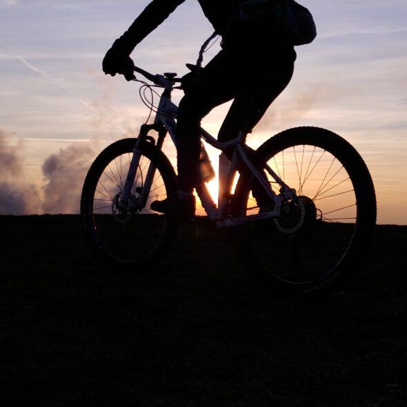 Cień osoby na rowerze na tle nieba