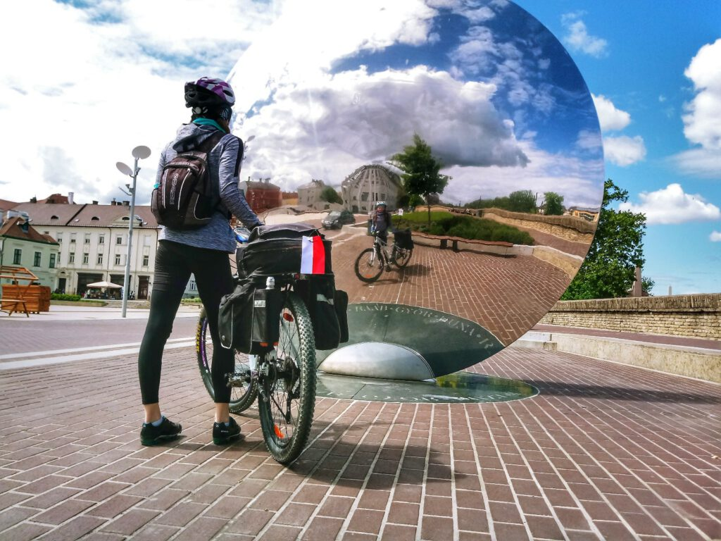 Osoba na rowerze przed okrągłym lustrem. W odbiciu niebo