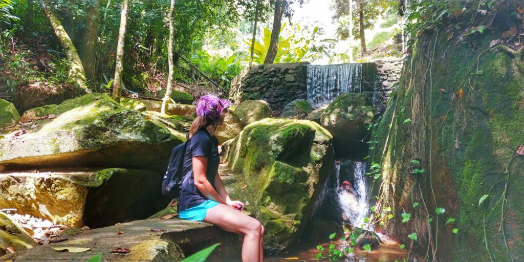 dziewczyna na tle wodospadu i skał porośniętych mchem