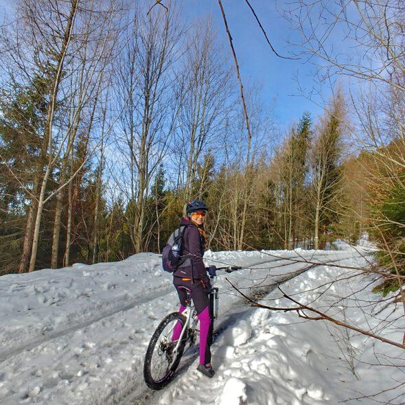 Ośnieżona droga w górach, dziewczyna na rowerze