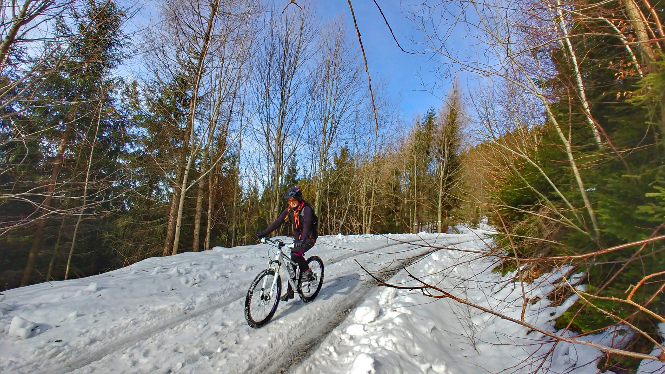 Górska zaśnieżona droga, dziewczyna jadąca na rowerze