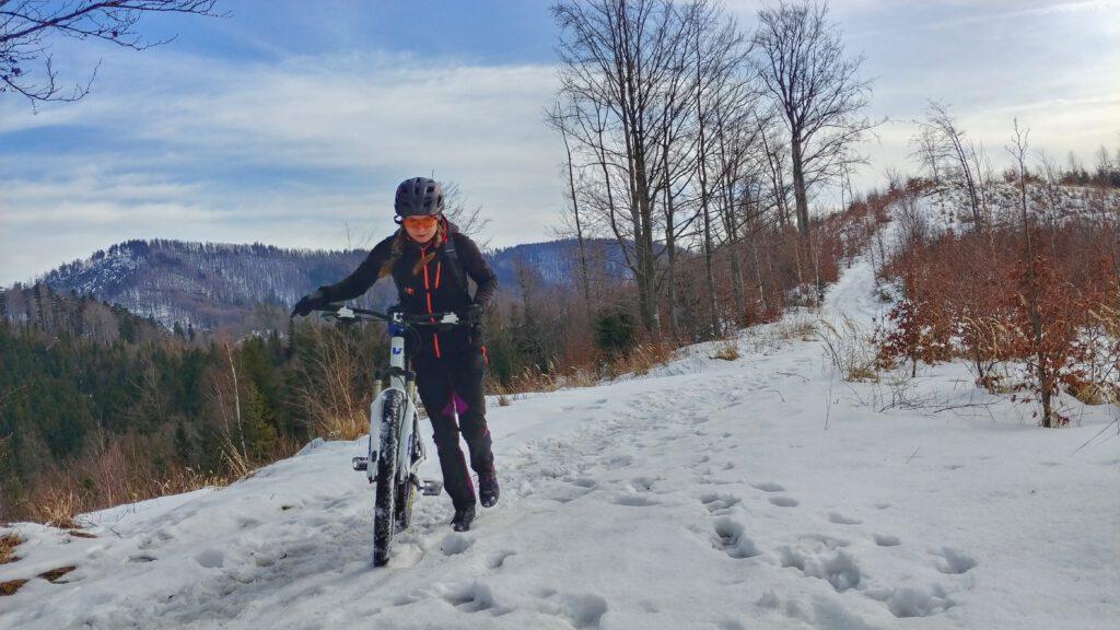 Dziewczyna prowadzi rower po śniegu