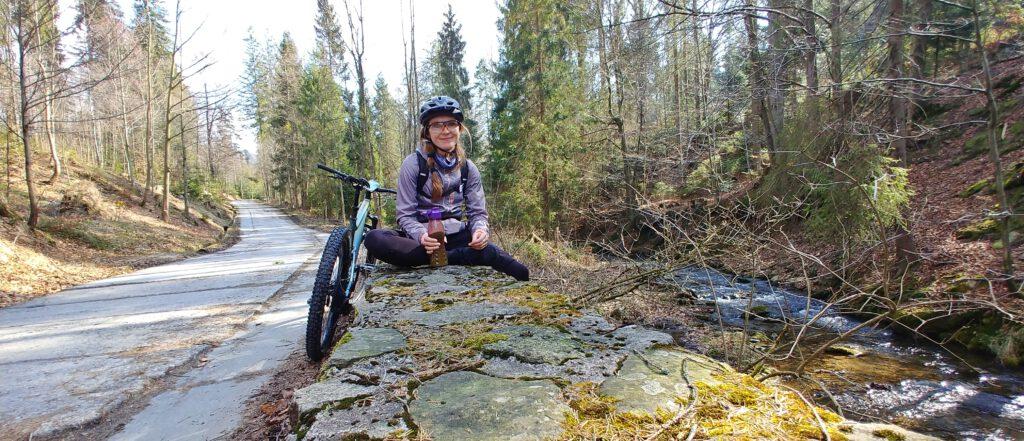 Dziewczyna z rowerem siedzi na murku