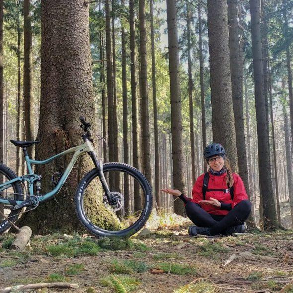 Dziewczyna siedzi w lesie obok rower