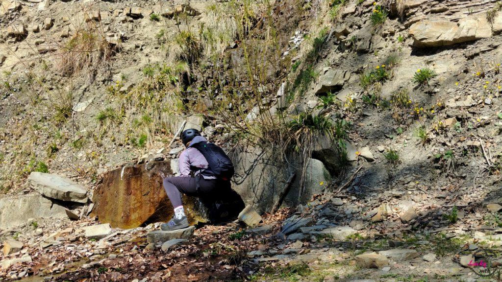 osoba nabiera wodę z górskiego źródła
