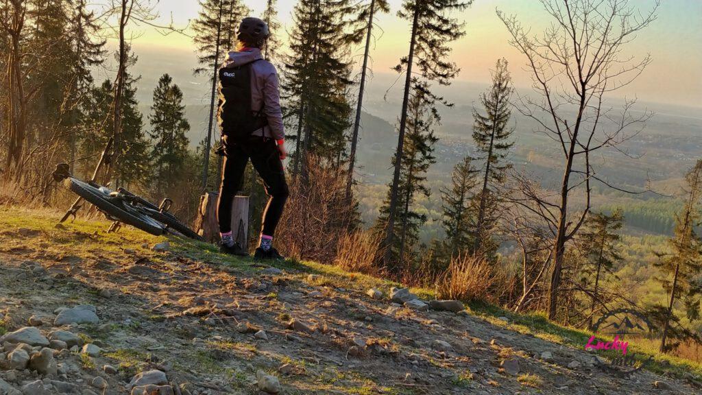 osoba patrzy na zachód słońca w górach