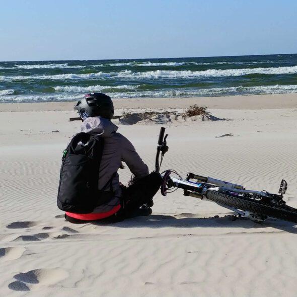 osoba siedzi na plaży z rowerem obok