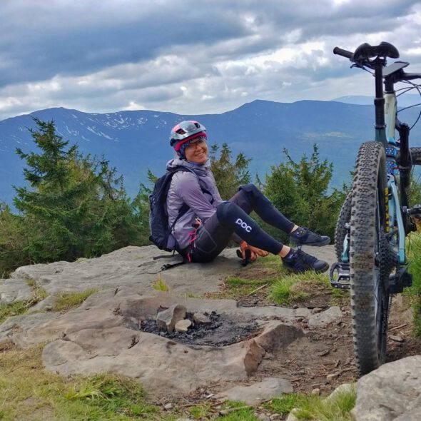 osoba siedzi na skale w tle góry