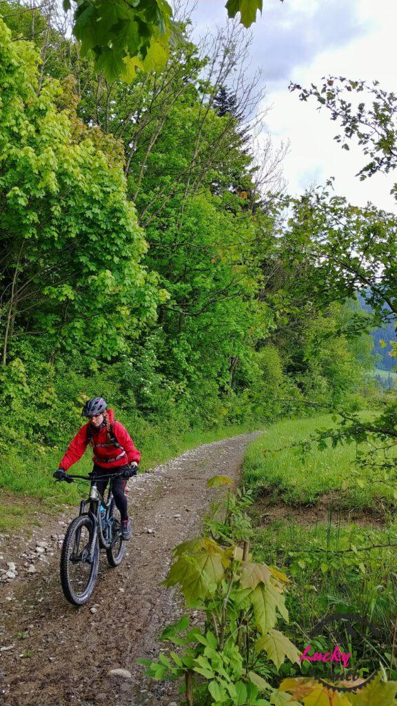 osoba na rowerze w czerwonej kurtce