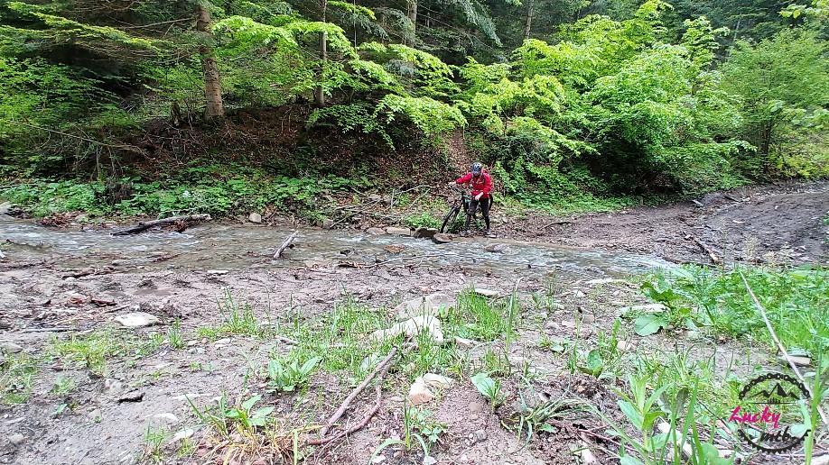 osoba przechodzi z rowerem przez rzekę