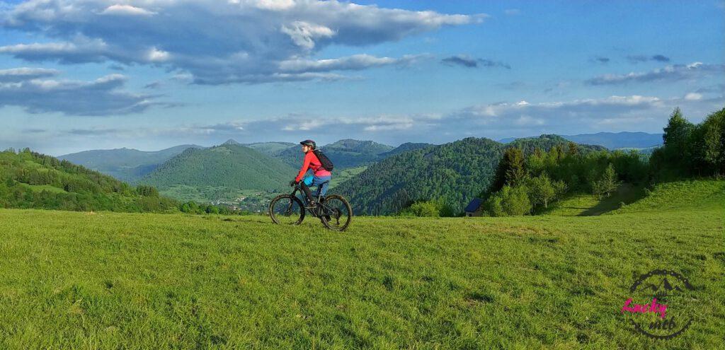 osoba jedzie na rowerze po łące na tle gór