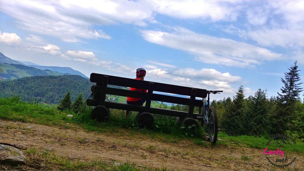 osoba siedzi na ławce w górach