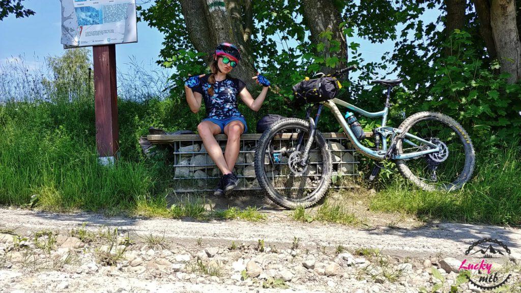 osoba siedzi na ławce z rowerem